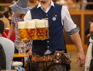 Oktoberfest, Munich, Germany. Waiter serving beers, closeup view
