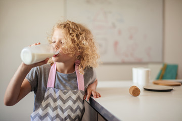Cute little curly blonde small girl drinling milk on white background while helping mother in the kitchen. Health and Child Beauty concept