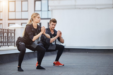 two fit young people bending knees to full squat position. side view full length photo. copy space.