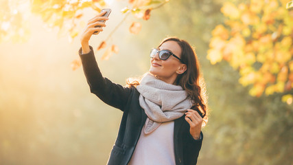 Portrait of pretty smiling brunette woman making selfie with smartphone In autumn sunny  garden