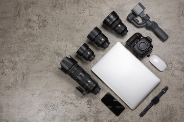 Photography equipment to travel on bare mortar background, DSLR camera,  Lenses, laptop, mouse, gimbal and smart watch