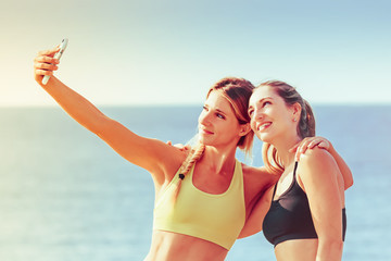 Two young women taking a selfie after a workout: girls taking pictures with a smartphone