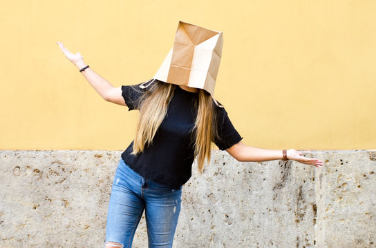 Young woman wearing a paper bag over her head in front of yellow background horizontal photo