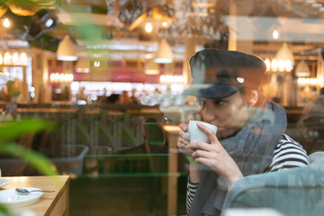 beautiful woman in hat and scarf drinking coffee while sitting in cafe