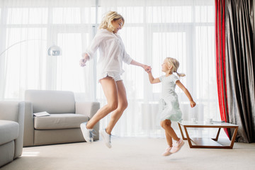 Cheerful mother and daughter, funny game at home