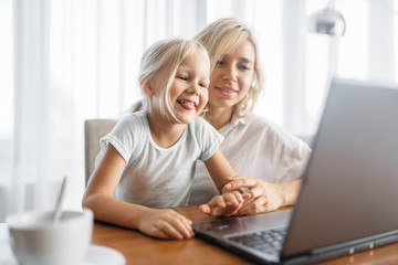 Smiling mother and child uses laptop at home