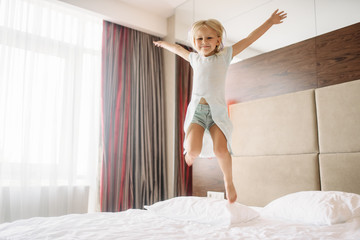 Little girl jumping on the bed in bedroom at home