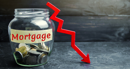 """Glass jar with coins and the inscription """"Mortgage"""" and down arrow. Reduced interest in the mortgage. Low interest rates. Falling real estate prices."""