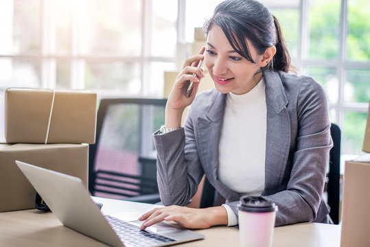 Happy young Asian woman answer phone from customer with her business online shopping at office.