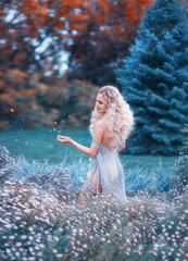 nice, kind and attractive healer with light curly hair wrestles gathers herbs for potion, holds a white chamomile in her hands and smiles, wears simple linen dress-shirt, wanders around flower field