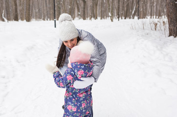 Winter, family and childhood concept - mother is walking with her daughter in snowy forest and hugging