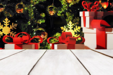 Empty wooden table on red gift box with christmas ornaments on sparkling christmas tree background, holiday concept and display products idea