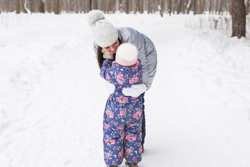 Family, children and nature concept - Young mother hug little happy child in the winter park