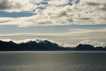 Mountains with clouds laying on mountain top under sunny blue sky with clouds looking across the ocean in Seward Alaska