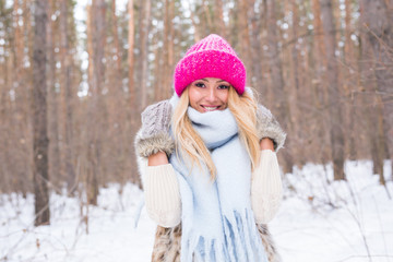 Beauty, winter and people concept - Attractive blonde woman in a pink sweater in the snowy forest is smiling