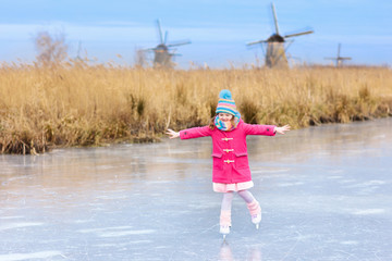 Child ice skating on frozen mill canal in Holland.
