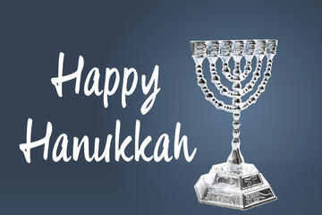 Happy Hanukkah and winter holidays concept with a silver menorah isolated on blue background with the text Happy Hanukkah in white next to it