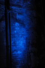Blue light shining on and old industrial brick wall