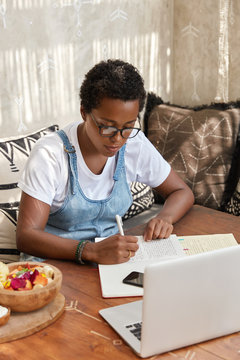 Shot of professional black graphic designer works remotely, sits in front of opened laptop, writes down ideas for new project, uses wireless internet, eats exotic fruit salad, prepares study planner