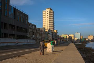 Los novios están caminando en el malecón de la Habana.