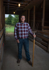 Young man in a barn with a pitch-fork