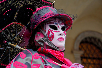 Colorful carnival pink-grey mask and costume at the traditional festival in Venice, Italy