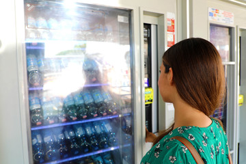 Young female backpacker tourist choosing a snack or drink at vending machine in Venice, Italy. Vending machine with girl.
