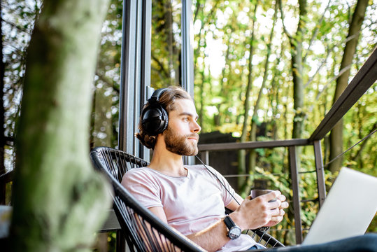 Poortrait of a handsome man working with laptop and headphones on the balcony of the house in the beautiful green forest