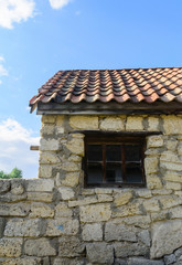 Window, stone wall and tile roof of an old building.