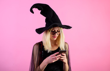 Woman in black dress and witch hat using smartphone. Message. Blonde woman witch using mobile phone, smart phone. Beautiful sensual sexy woman with cellphone. Modern technology and leisure concept.