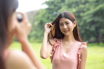 Woman using camera to take photo friend at garden. Women resting at garden in holiday. People with lifestyle, relax, holiday concept.