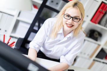 A young girl working at a computer in the office.