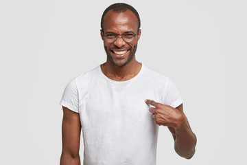 Cheerful dark skinned guy with toothy smile, points at blank space of his t shirt for your advertising content or logo, wears round spectacles, involved in advert campaign. Clothing, monochrome
