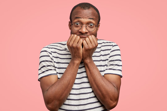 Photo of anxious young black man bites finger nails with worried expression, worries before some important event, isolated over pink background. People, ethnicity and facial expressions concept