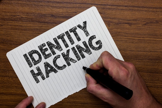 Writing note showing  Identity Hacking. Business photo showcasing criminal that steal your personal information using malware Man holding marker notebook paper expressing ideas wooden background