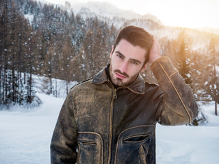 Stylish man walking confidently looking away on territory of contemporary winter resort covered in snow in the mountain, wearing brown leather jacket