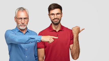 Cheerful friendly men of different generations involved in advertising campaign, wear spectacles, point together aside, demonstrate something. Two bearded partners show way to office building