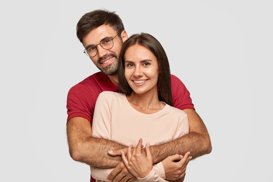 Lovely couple have warm cuddle, pose for family portrait, smile joyfully, have good relationships. Affectionate brother embraces his sister isolated over white wall. Girlfriend and boyfriend have date