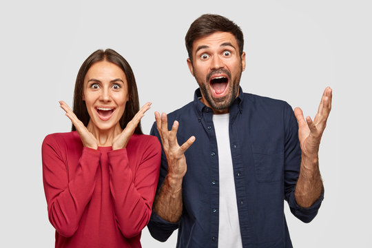 People, friendship and happiness concept. Happy joyful young Caucasian woman and man excaim loudly, being in high spirit, keep mouth opened, notice something unbelievable, isolated on white wall.