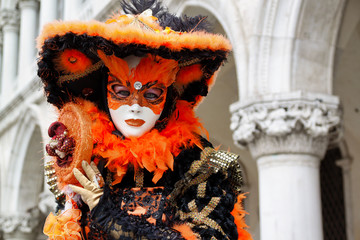 Colorful carnival black-orange mask and costume at the traditional festival in Venice, Italy