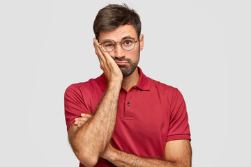 Indoor shot of sad man looks bored, keeps hand on cheek, dressed in red casual clothes, feels lonliness, doesnt know what to do, poses against whitte studio wall. Tired European male stands indoor