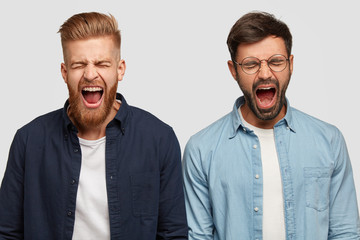 Photo of annoyed guys produce loud yell, open mouth widely, have trendy haircut and bristle, stand shoulder to shoulder against white background. People, irritation and negatie facial expressions