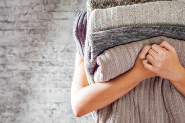 woman holding in hands Stack of cozy knitted sweaters on gray wall background