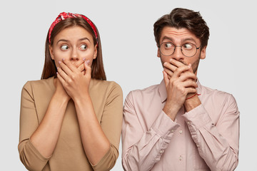 Wall Mural - Wow, what secret! Amazed lady and guy cover mouthes and look at each other with myterious surprised expressions, stand next to each other, dressed in fashionable clothes, isolated over white wall