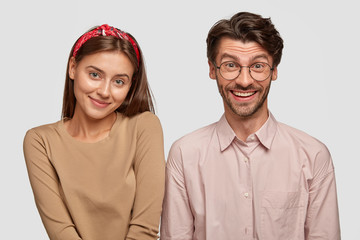 Wall Mural - Image of friendly fellows smile happily, stand next to each other, being in high spirit, have date together, isolated over white background. Smiling unshaven man and his girlfriend model indoor