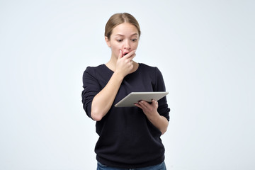 Shocked woman looking at digital tablet with surprise and shock over gray background. Astonishment or hot news in internet