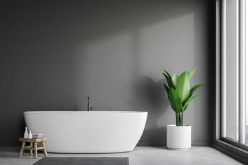 White tub in gray bathroom interior