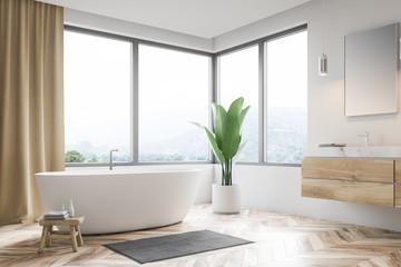 Corner of white bathroom, tub and sink