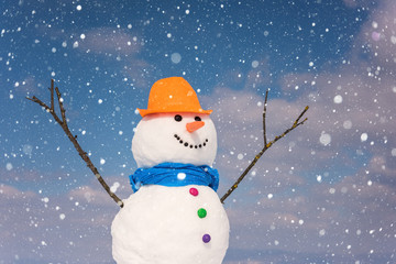 Cute smiling snowman against blue sky background with falling snowflakes, happy winter concept