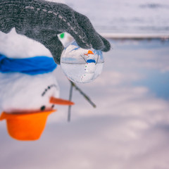 Cute smiling snowman in glass ball, sunny day, happy winter concept